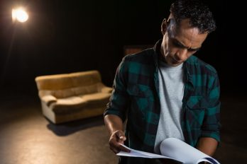 Actor reading their scripts on stage